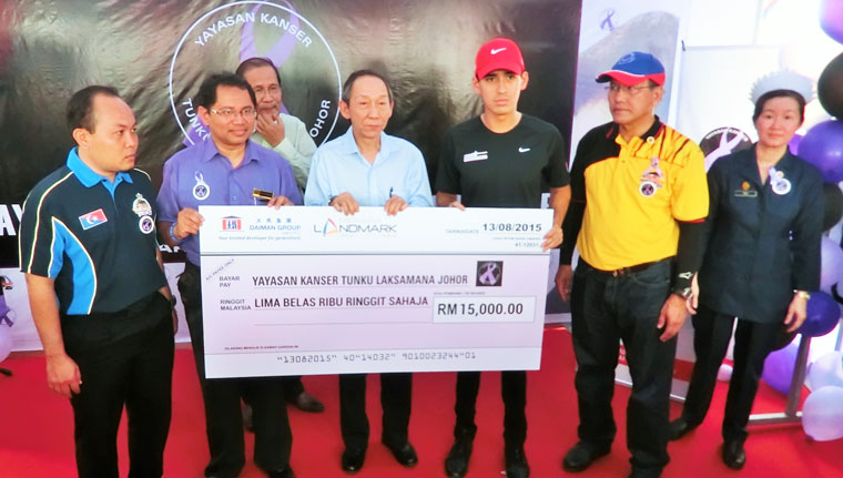 Thanks: Tay (centre) presenting the mock cheque to Tunku Abdul Rahman (second from right).